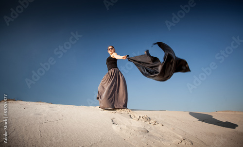 woman with black cloth walking on sand dunes