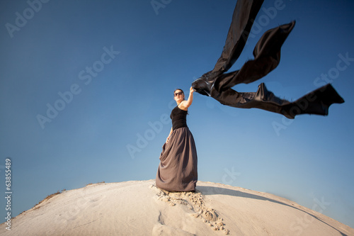 woman holding black cloth on sand dune at windy day