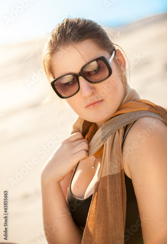 woman in sunglasses and scarf at desert