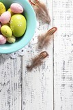 Easter eggs in color bowl on color wooden background