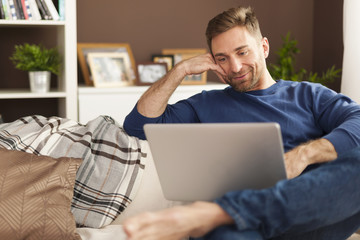 Handsome smiling man relaxing with laptop at home