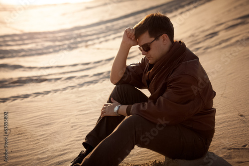 handsome man sitting and thinking on sand dune