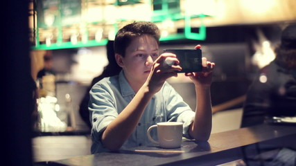Teenager taking photo with smartphone in cafe at night