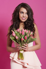 Smiling elegant woman with pink tulips