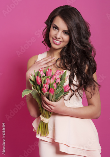 Grateful smiling woman with bouquet of fresh tulips