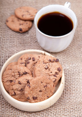 Chocolate chip cookies in a wooden bowl on a hessian background