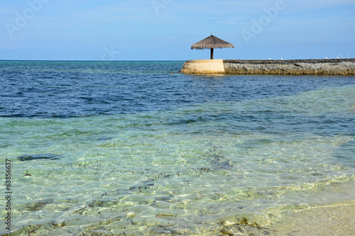 Wild beach with marine pier and umbrella Maldives