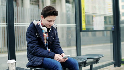 Young teenage boy texting on smartphone, waiting for bus