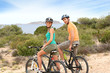 Couple riding mountain bikes on mediterranean island