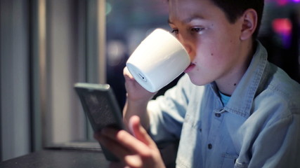 Young teenage boy with smartphone sitting in cafe