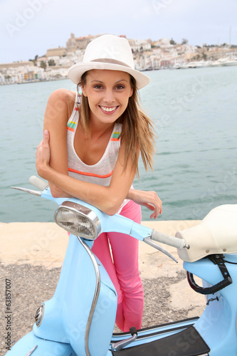 Smiling girl standing by vintage scooter in front of Ibiza city
