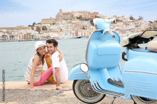 Portrait of cheerful couple sitting on the harbour of Ibiza