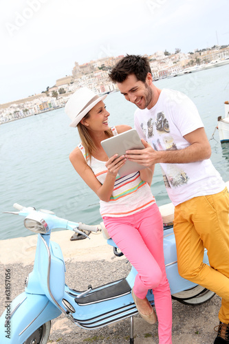 Couple of tourists websurfing with tablet, town of Ibiza