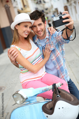 Couple sitting on scooter and taking picture of themselves