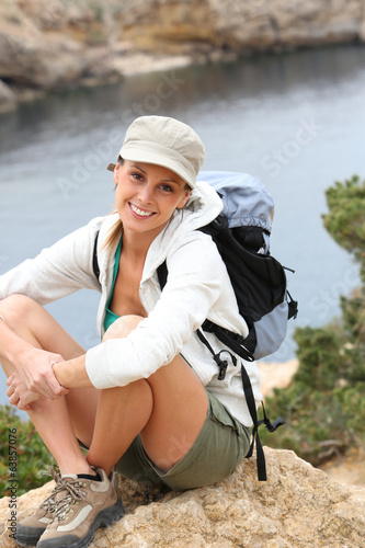 Portrait of cheerful hiking girl with backpack
