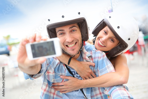Couple taking picture of themselves on scooter