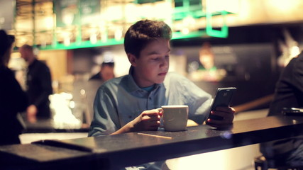 Young teenage boy with smartphone, drinking coffee, in cafe