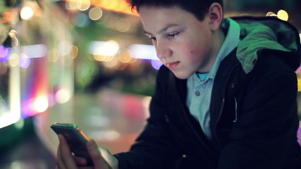 Young teenager texting on smartphone in the city at night