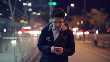 Young boy with smartphone walking in the city at night