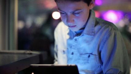 Young boy with tablet computer in cafe