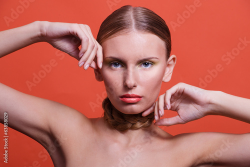 Beauty portrait of a girl with her hands on an orange background
