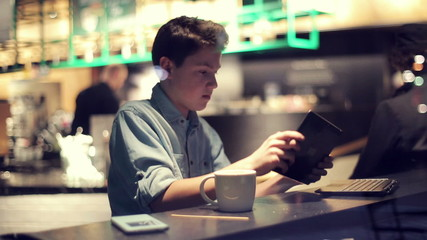 Young teenager playing game on tablet computer in cafe