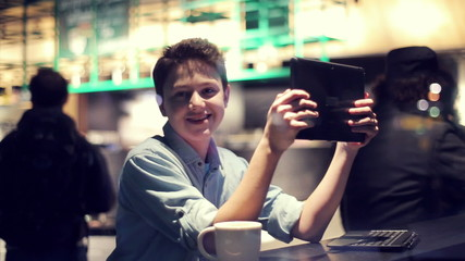 Happy young boy with tablet computer in cafe