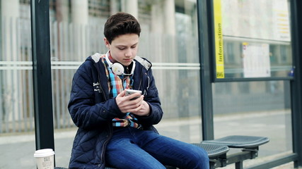 Young teenager waiting for bus on bus stop in the city
