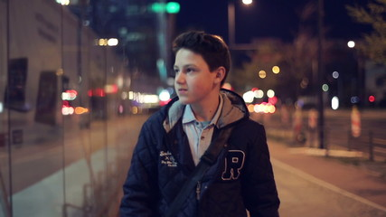 Young confident teenager walking in the city at night