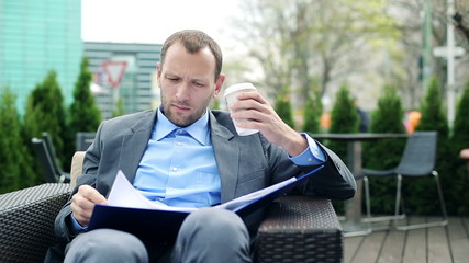 Businessman reading documents, drinking coffee in cafe