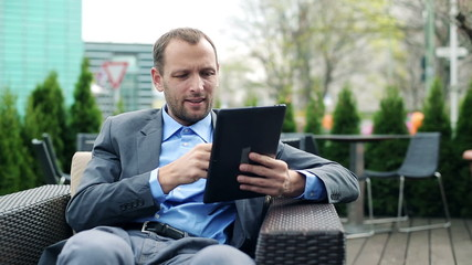 Businessman with smartphone and tablet computer working in cafe