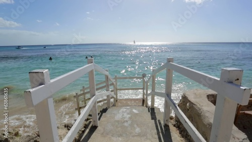 Stairs in front of the ocean on a sunny day and blue sky