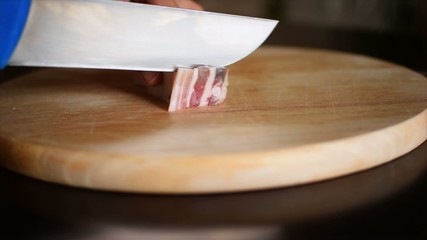 Slicing pork bacon on the cutting surface