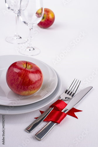 Celebration table set with red apples on white