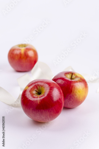 Three red apples on white background and ribbon
