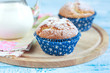 Close-up of two homemade orange muffins with a jug of milk, sele