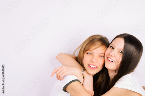 blonde and brunette teen girls cuddling and laughing
