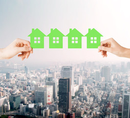 man and woman hands with many green paper houses