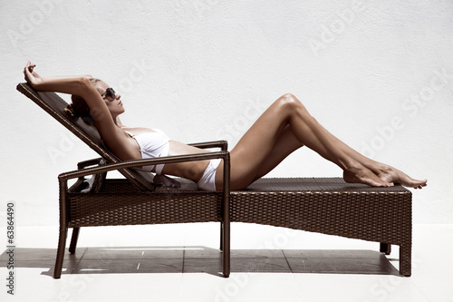 Beautiful tan female model sunbathing in bikini on chaise-longue
