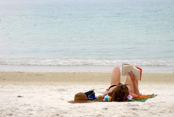 Woman sunbather is reading a book on the beach in Thailand