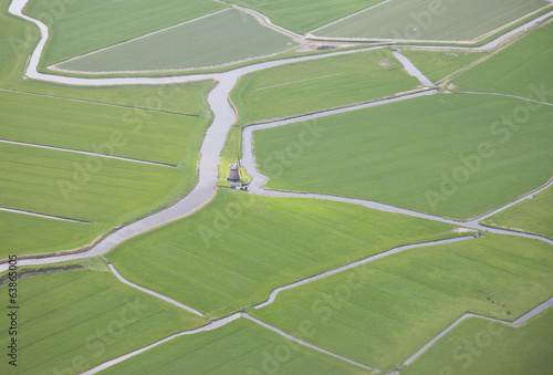 Green landscape with water and windmill from above