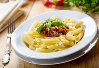 plate of penne pasta with bolognese sauce