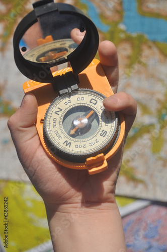 Compass on his palm against the background maps