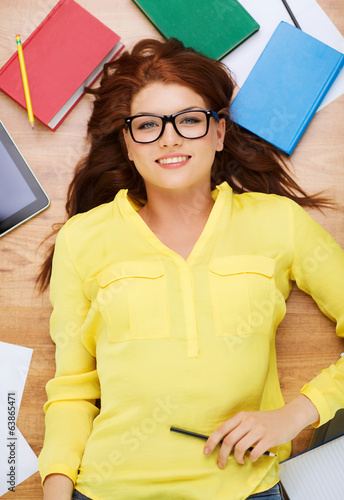 smiling female student in eyeglasses with pencil