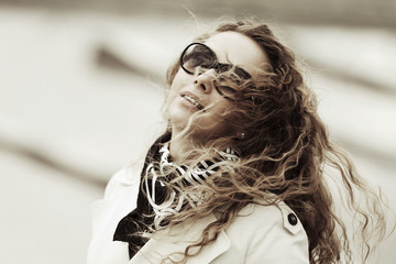 Happy woman with long curly hairs in the wind