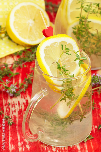 Lemon juice. Pitcher and Glass of Lemonade with Fresh Lemons