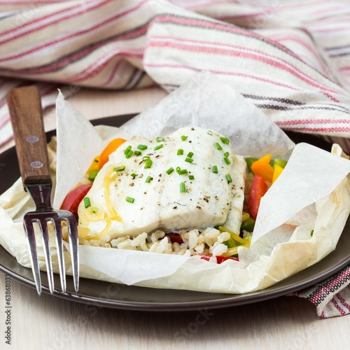 White fish fillet baked in paper, parchment with rice, pepper