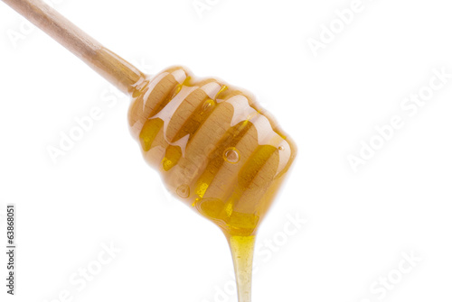 Honey dripping from a wooden spoon.