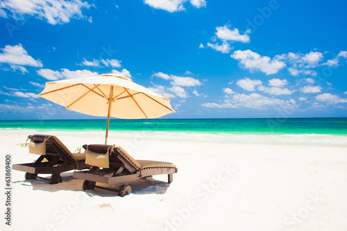 canvas print picture two beach chairs and umbrella on sand beach. Holidays