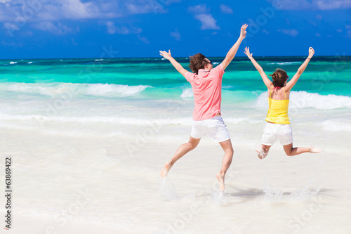 Young couple in bright clothes jumping on the beach
